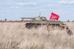 2018-04-30 Samara Region, Rússia Um comandante com uma bandeira conduz na batalha de soldados soviéticos Reconstrução do hostil Imagem de Stock Royalty Free