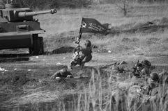 2018-04-30 Samara region, Rosja Ofensywa żołnierze Radziecki wojsko z flaga na pozyci Niemiecki oddział wojskowy obraz stock