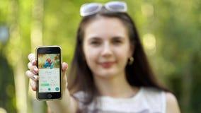 Samara, Rusia - 6 de agosto de 2016: la mujer que juega el pokemon va en su iphone juego multijugador con los elementos de aument Imagenes de archivo