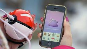 Samara, Rusia - 8 de diciembre de 2016: la mujer que juega el pokemon va en su iphone el pokemon va juego multijugador con los el Imagen de archivo