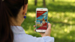 Samara, Russia - July 4, 2017: woman playing pokemon go on his iphone 6s plus. pokemon go multiplayer game with elements. Of augmented reality stock image