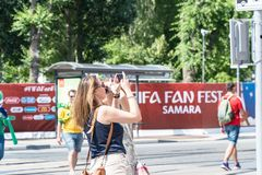Girls tourists take pictures on the street during the world Cup 2018. SAMARA, RUSSIA - JUNE 21, 2018: Girls tourists take pictures on the street during the world Stock Photo