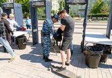 People pass through police frames metal detectors. Samara, Russia - May 12, 2017: People pass through police frames metal detectors at the city street in summer stock photo