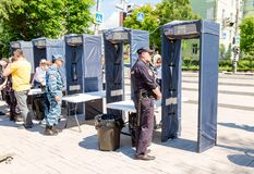 People pass through police frames metal detectors. Samara, Russia - May 12, 2017: People pass through police frames metal detectors at the city street in summer stock images