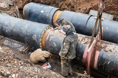Repair work of heating duct. The workers, welders made by electric welding on large iron pipes at a depth of excavated trench. Samara, Russia - October 1, 2017 stock images