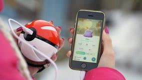 Samara, Russland - 8. Dezember 2016: die Frau, die pokemon spielt, gehen auf sein iphone pokemon gehen spiel mit Elementen von Mu Stockbild