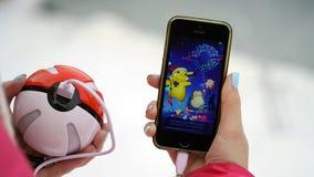 Samara, Russland - 15. Dezember 2016: die Frau, die pokemon spielt, gehen auf sein iphone pokemon gehen spiel mit Elementen von M Lizenzfreie Stockfotografie