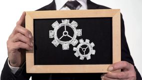 Samarbeta tandhjul som dras på svart tavla i affärsmanhänder, teamwork arkivfoton