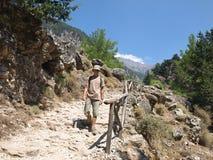 Samaria gorge - the most popular tourist destinati. Mountain path in Samaria gorge. Young man walking royalty free stock photography
