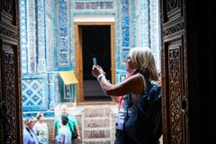 A european lady taking pictures at Shohizinda ensemble stock photography