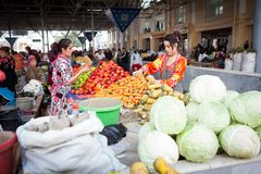 Women negotiating prices at main market bazaar, one of them is picking vegetables to buy stock image