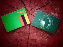 Sambianische Flagge mit Flagge der Afrikanischen Union auf einem Baumstumpf Lizenzfreie Stockbilder