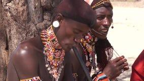 Samburu stammedlem som spelar den traditionella blåsinstrumentet lager videofilmer