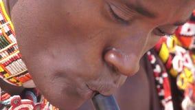 Samburu tribesman playing traditional wind instrument.