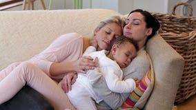 Same sex couple asleep with son