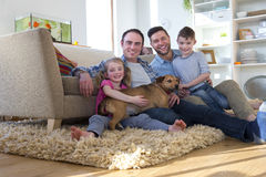 Same sex couple with children and dog. Same sex male couple sitting on the floor in their living room with their son and daughter. Their pet dog is lying across Stock Photo