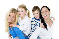 Same sex couple with children. Same sex female couple posing in front of a white background with their son and daughter on their backs stock image