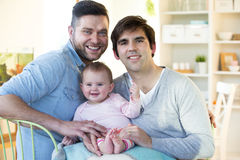 Same sex couple with daughter at home. Same sex male couple sitting at home smiling for the camera with their daughter on their lap Royalty Free Stock Photo