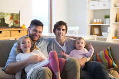 Same sex couple with daughters at home. Same sex male couple smiling for the camera with their duaghters at home Royalty Free Stock Photo