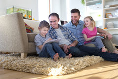 Same sex couple at home with children. Same sex male couple sitting on the floor of their front room with their children, helping them do their homework Stock Image