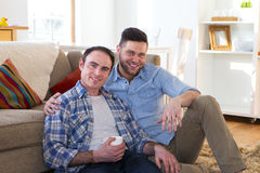 Same sex couple at home. Same sex male couple sitting together in their front room on the floor. One men is holding a coffee whilst the other has his arm round Royalty Free Stock Photo