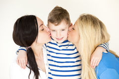 Same sex couple kissing their son. Same sex couple kissing eitherside of their sons face for the camera Royalty Free Stock Photos