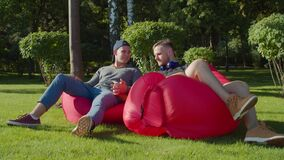 Same-sex couple relaxing on bean bags in nature
