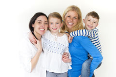 Same sex couple with their children. Same sex female couple posing with their son and daughter in front of a white background Royalty Free Stock Photos