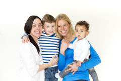 Same sex couple with their sons. Same sex female couple posing with their two sons in front of a white background Royalty Free Stock Photography