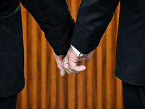 Same-Sex Marriage. Two gay men stand hand in hand before the marriage altar having just been legally married under Same-Sex Marriage legislation.  Their bodies Stock Image