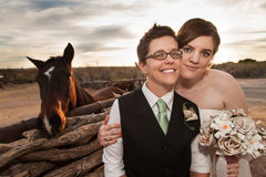 Same Sex Newlyweds with Horse. Boyish groom and lesbian bride outdoors near horse Stock Photography