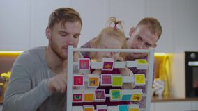 Same sex parents helping kid learning abc at home