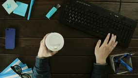 At the same time drinking coffee and typing on a keyboard. At the same time drinking coffee and typing on a keyboard on his desk. Paraphernalia on the table in stock footage
