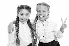On same wave. Schoolgirls wear formal school uniform. Sisters little girls with braids ready for school. School fashion stock photo