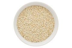 Samen des indischen Sesams in der weißen Schüssel, lokalisiert auf weißem Hintergrund stockbild