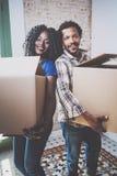 Samen het glimlachen van jonge zwarte Afrikaanse paar bewegende dozen in nieuw huis en het maken van het succesvol leven Vrolijke Stock Foto's