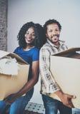 Samen het glimlachen van jonge zwarte Afrikaanse paar bewegende dozen in nieuw huis en het maken van het succesvol leven Vrolijke Royalty-vrije Stock Afbeeldingen