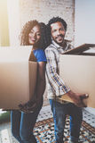 Samen het glimlachen van jonge zwarte Afrikaanse paar bewegende dozen in nieuw huis en het maken van het succesvol leven Vrolijke Royalty-vrije Stock Fotografie