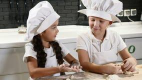 Samen het koken Twee kinderen in het rollende deeg van de chef-kokhoed in huiskeuken Het restaurant van het twee jonge geitjesspe stock footage