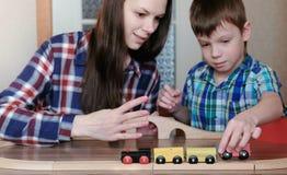 Samen het spelen Het mamma en de zoon spelen een houten spoorweg met trein, wagens en tunnelzitting bij de lijst royalty-vrije stock afbeelding