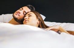 Samen houdend van jonge paarslaap in een bed met witte bladen thuis - de ogenblikken van het Leven van mensen in liefde in de sla stock afbeeldingen
