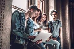 Samen surfend netto Groep gelukkige jongeren die en laptop bekijken terwijl het zitten bij de venstervensterbank samenwerken royalty-vrije stock afbeelding