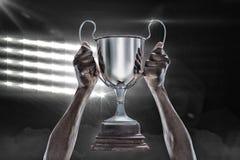 Samengesteld beeld 3D van bebouwde hand van de trofee van de atletenholding Royalty-vrije Stock Fotografie