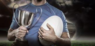 Samengesteld beeld 3D van de holdingstrofee en bal van de rugbyspeler Stock Afbeeldingen