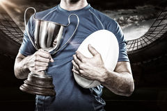 Samengesteld beeld 3D van de holdingstrofee en bal van de rugbyspeler Royalty-vrije Stock Foto