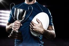 Samengesteld beeld 3D van de holdingstrofee en bal van de rugbyspeler Royalty-vrije Stock Foto's