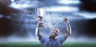 Samengesteld beeld 3D van gelukkige omhooggaand en sportman die terwijl het houden van trofee kijken toejuichen Stock Foto