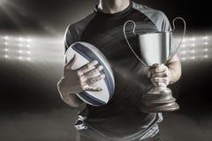 Samengesteld beeld 3D van midsection van succesvolle de holdingstrofee en bal van de rugbyspeler Royalty-vrije Stock Afbeelding