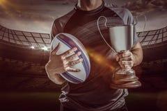 Samengesteld beeld 3D van midsection van succesvolle de holdingstrofee en bal van de rugbyspeler Stock Afbeelding