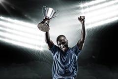 Samengesteld beeld 3D van portret van gelukkige sportman die terwijl het houden van trofee toejuichen Stock Foto's